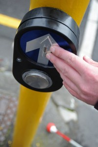 Person about to push button at pedestrian crossing