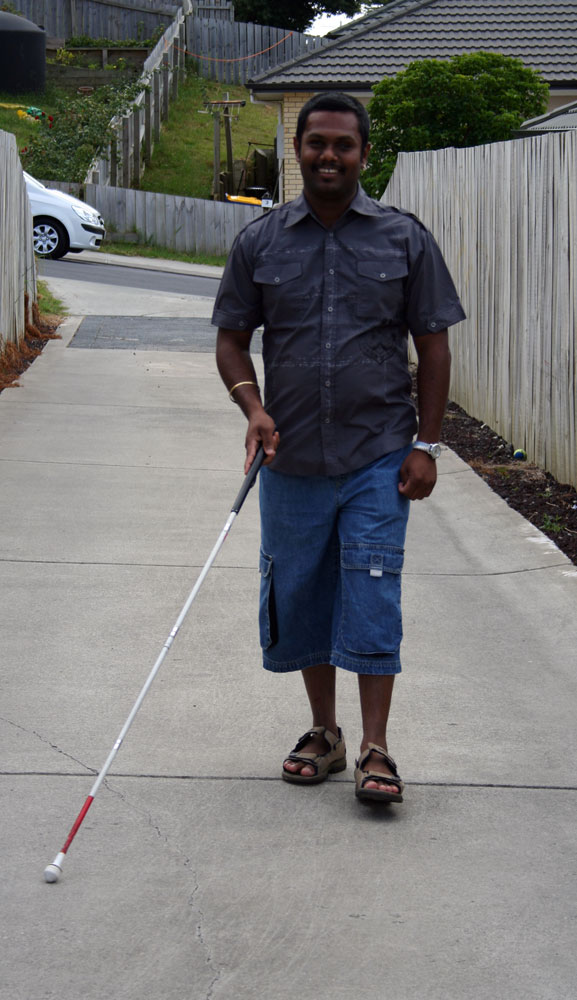 a man walking down the a driveway with a white cane