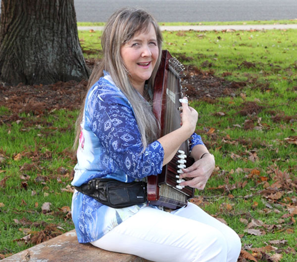 Jacqui sitting on a bench playing her autoharp