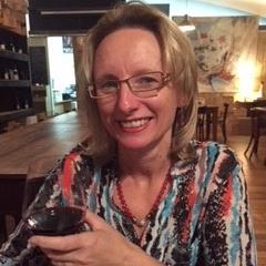 Image shows Dena Harnett holding a glass of wine.